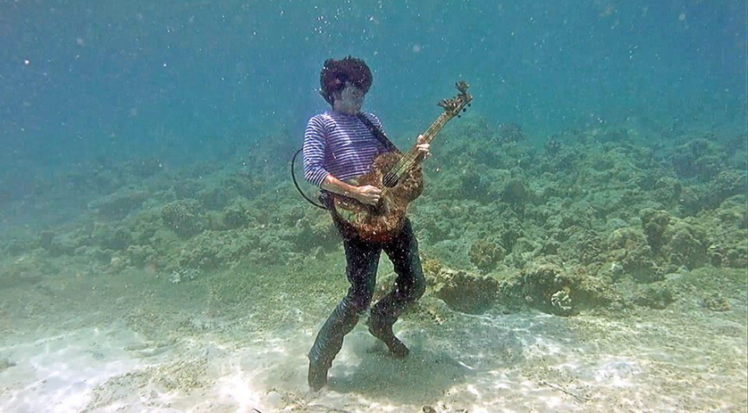 Sasha Mizgulin, lead singer of Egoists playing his guitar underwater in video for Maiden of the Sea
